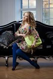 Beauty woman in luxurious sofa with handbag Stock Images