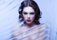 Beauty woman model with makeup through mirror Stock Images