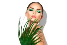 Beauty woman with natural green palm leaf. Portrait of model girl with perfect makeup, green eyeshadows stock photography