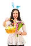 Beauty woman offering basket with Easter eggs Stock Photos