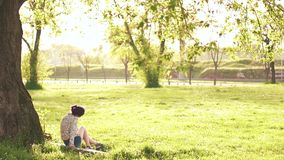Beauty woman Outdoors sitting under the tree stock video footage
