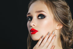 Beauty Woman with Perfect Makeup and brown hairs. Beautiful Professional Holiday Make-up. Smoky eyes. Red Lips  Nails Royalty Free Stock Photo