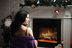 Beauty woman, perfect smile resting on the floor at home with a fireplace. In the background stock photography