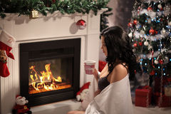 Beauty woman, perfect smile resting on the floor at home with a fireplace. In the background royalty free stock photo