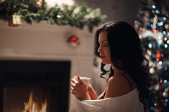 Beauty woman, perfect smile resting on the floor at home with a fireplace. In the background stock photo