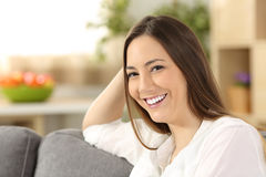 Beauty woman with perfect white smile at home. Single beauty woman with perfect white teeth smiling and looking at you sitting on a sofa in the living room at Royalty Free Stock Images
