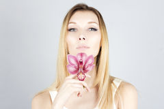 Beauty woman with pink flower in hand. Clear and fresh skin. Beauty face. Royalty Free Stock Photography