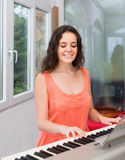 Beauty woman playing piano at home Stock Photography
