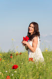 Beauty woman in poppy field in white dress holding a poppies bouquet Stock Photos