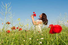 Beauty woman in poppy field in white dress holding a poppies bouquet Royalty Free Stock Photos