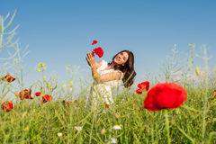 Beauty woman in poppy field in white dress holding a poppies bouquet Royalty Free Stock Photo