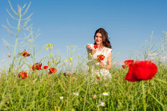 Beauty woman in poppy field in white dress holding a poppies Stock Photography