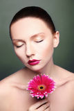 Beauty woman portrait bright backround holding. Gerbera flower Royalty Free Stock Photography
