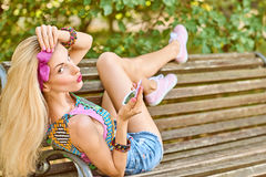 Beauty woman primping in park, lifestyle, people. Beauty stylish playful woman primping with mirror on bench, park, people, outdoors.Attractive hipster happy stock images