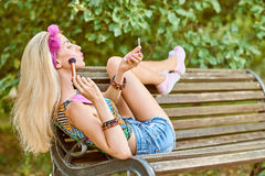 Beauty woman primping in park, lifestyle, people. Beauty stylish playful woman primping with mirror on bench, park, people, outdoors.Attractive hipster happy stock photography