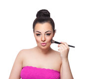 Beauty woman putting bronzer on her cheeks Royalty Free Stock Image