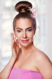 Beauty woman putting cream on her face Stock Photos