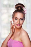 Beauty woman putting cream on her face Royalty Free Stock Images
