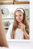 Beauty woman putting lipgloss on royalty free stock image