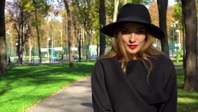 Beauty woman with red lips in hat with wide brim. And stylish coat looking at the camera outdoors in the autumn park royalty free stock photos