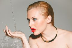 Beauty woman with red lips.  Splashing water on her hand. Royalty Free Stock Image