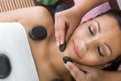 Beauty woman relaxing in spa. Stone massage. royalty free stock photography