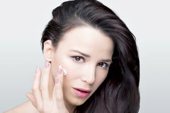 Beauty woman. Beauty shot of a woman applying face cream on her face Stock Photos