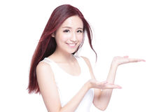Beauty woman show something. Beauty woman with charming smile and show something to you with health skin, teeth and hair  on white background, asian beauty Royalty Free Stock Image
