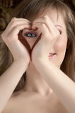Beauty woman showing heart. And looking through Royalty Free Stock Images