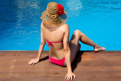 Beauty Woman Sitting on edge of Swimming Pool. A young woman wearing a red bikini and pamela sitting on edge of a pool. Backward Stock Photos
