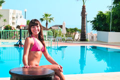 Beauty woman sitting near pool Stock Photo