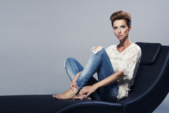 Beauty woman sitting on sofa Stock Photography