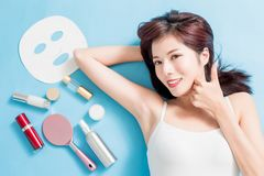 Beauty Skin care concept. Beauty woman smile and show thumb up with her skin care product - she is lying on the blue floor royalty free stock photography