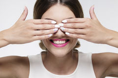 Beauty woman smiling hiding her eyes with gel nails Royalty Free Stock Images