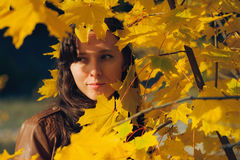 Beauty woman standing in yellow autumn leaves Stock Photo