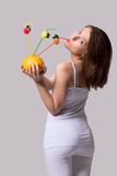 Beauty woman stands back and drink from orange juice with straw. Royalty Free Stock Photos