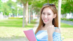 Beauty woman student. Smile and show fist in the school Stock Image