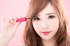 Beauty woman take mascara. On the pink background Royalty Free Stock Photography