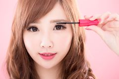 Beauty woman take mascara. On the pink background Stock Photography