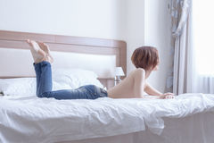 Beauty woman topless lay on bed look at window Royalty Free Stock Images