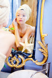 Beauty woman with towel looking at golden mirror Royalty Free Stock Images