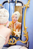 Beauty woman with towel looking at golden mirror Stock Photos