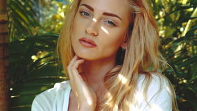 Beauty woman in tropcial garden. Closeup face of stunning blond woman in white dress with light makeup looking at the camera and posing in tropical palm trees stock footage