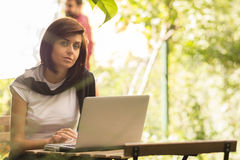 Beauty woman using laptop sitting at an outdoor coffee shop Royalty Free Stock Photos