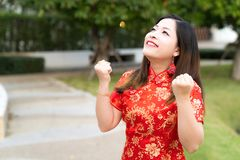 Beauty woman wear cheongsam and feel excited with chinese new year on nature background. She wears bracelets, gold rings and royalty free stock photos