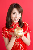 Beauty woman wear cheongsam. And show gold piggy bank to you in chinese new year Stock Photos