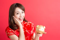 Beauty woman wear cheongsam. And show gold piggy bank to you in chinese new year Stock Photo