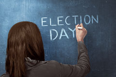 Beauty woman writing a 'ELECTION DAY' on blue chalkboard. Election day background or concept stock image