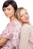 Beauty women. Two young beauty women sitting back to back on white background Royalty Free Stock Images