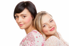 Beauty women. Two young beauty women sitting back to back on white background Royalty Free Stock Image